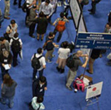 People in a crowd at a conference looking at bulletin boards